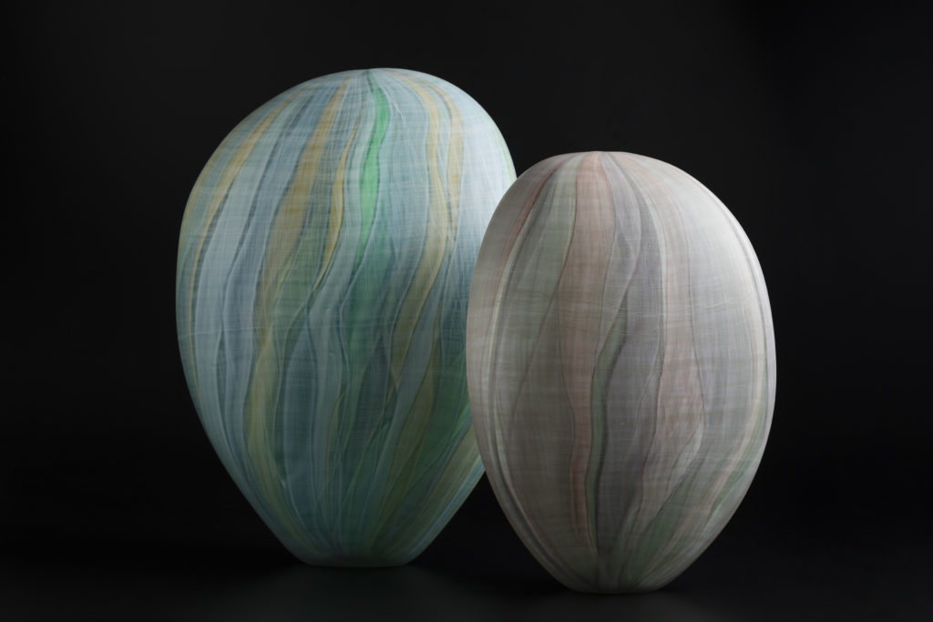 A pair of coloured glass forms standing upright against a black background. The form on the left is slightly larger and is decorated with vertical bands of in green, blue and yellow. The smaller piece ion the right shows bands in dusty pink, grey and green hues.