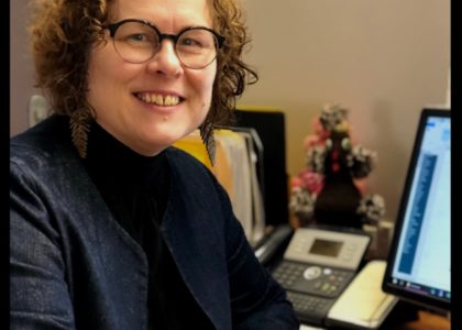 A woman with glasses and curly hair sits at an office desk.