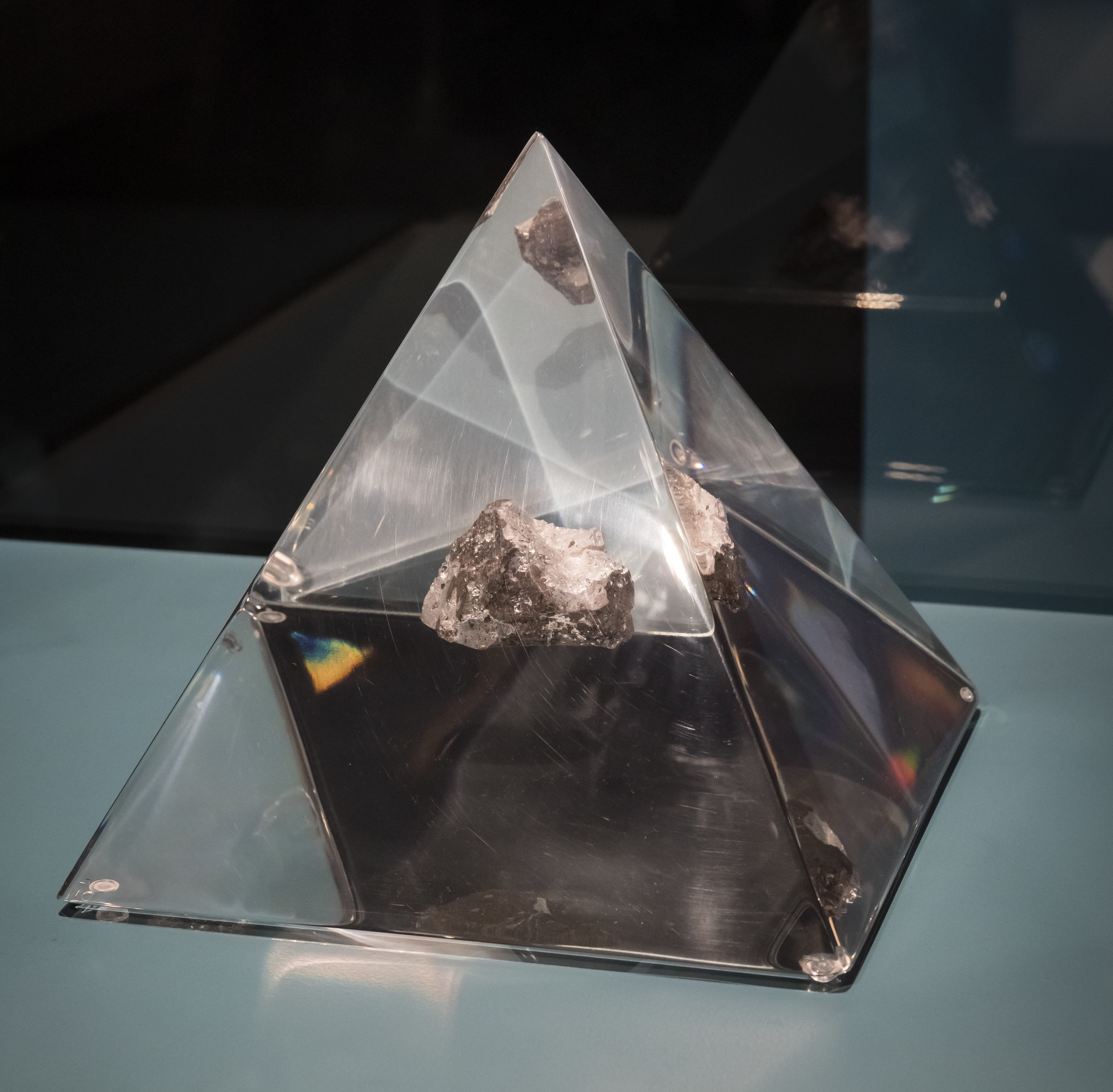 A small piece of rock, appoximately 3cm in diameter, encased in a perspex pyramid.