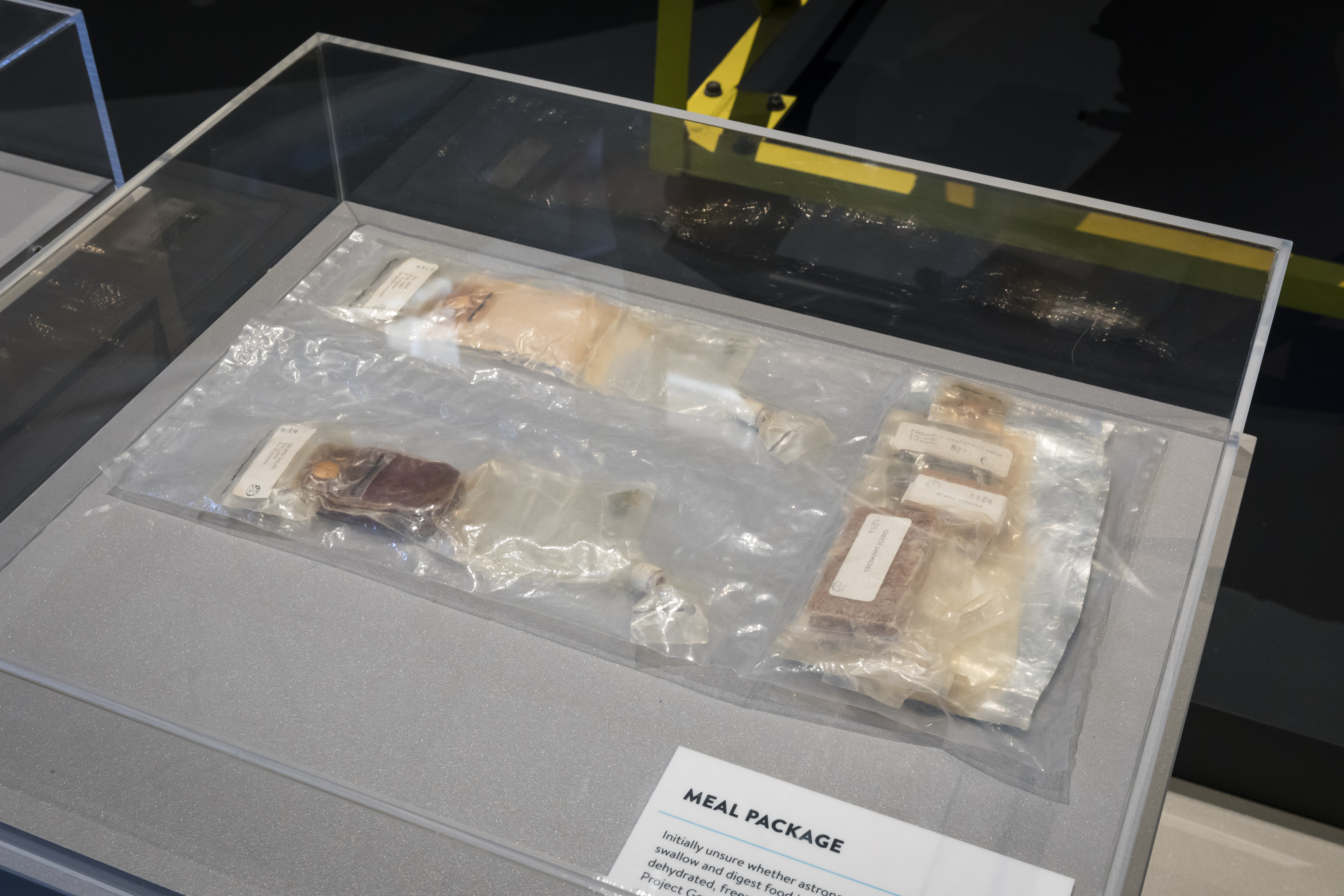 A large clear plastic bag, inside which are individual pouches of food, some of which have been fitted with nozzles for easy consumption in space.