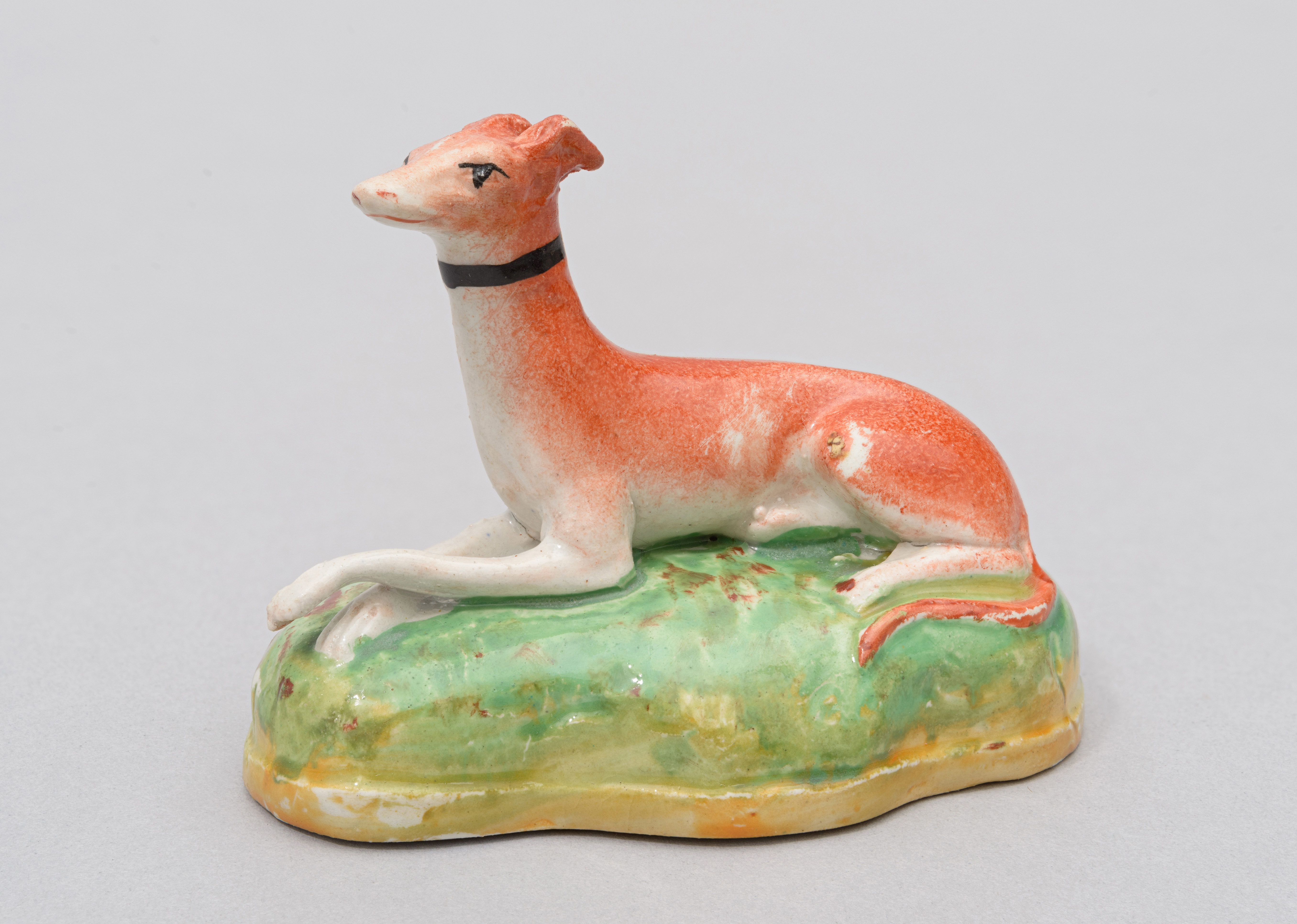A ceramic figure of a greyhound dog with red coat and a black collar. The greyhound is sitting on a green grassy patch.