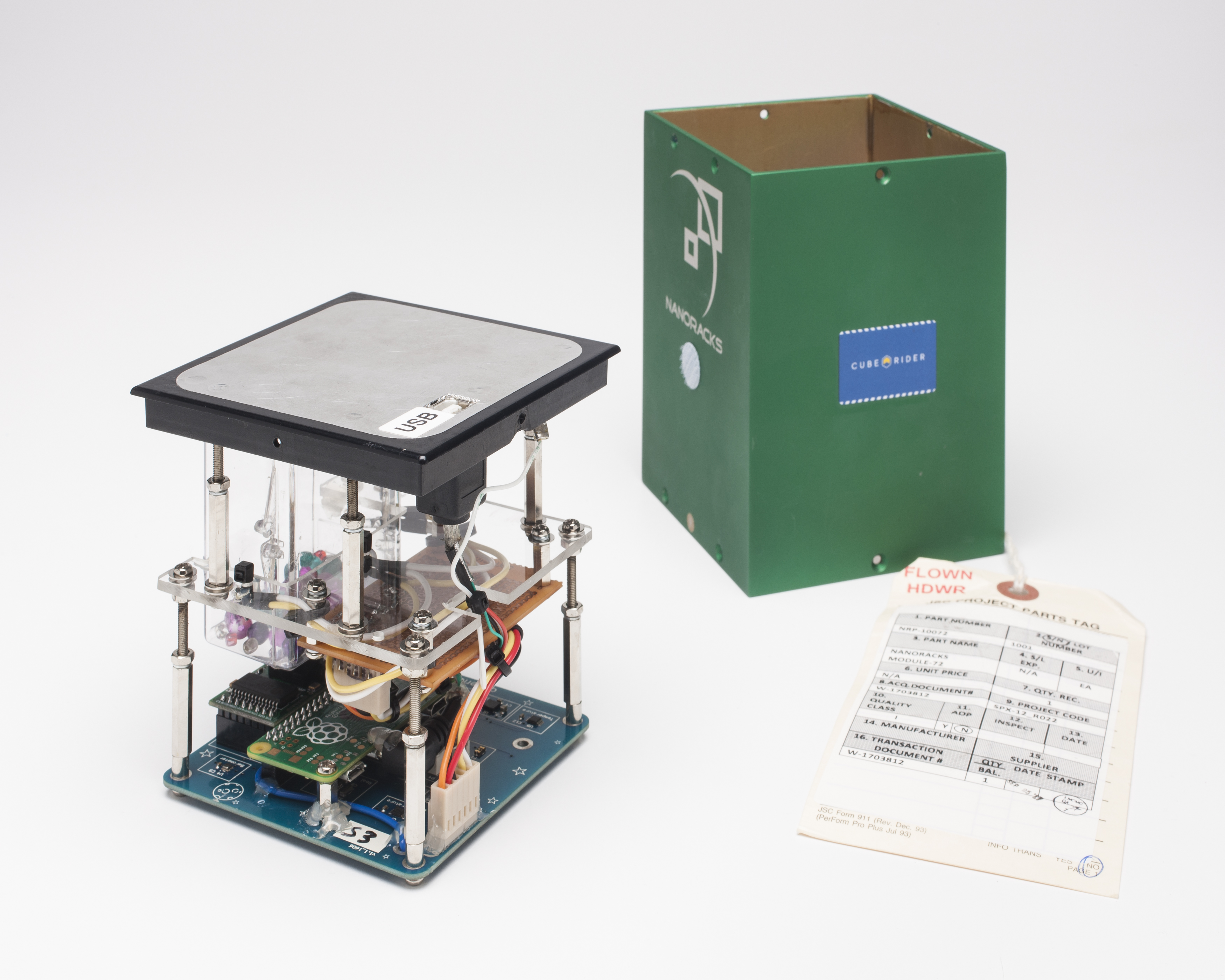 A rectangular unit about 15cm high, comprising a series of electronics. On the right is a green metal case for the device, and attached to it a paper label stamped with the words 'FLOWN HDWR'.
