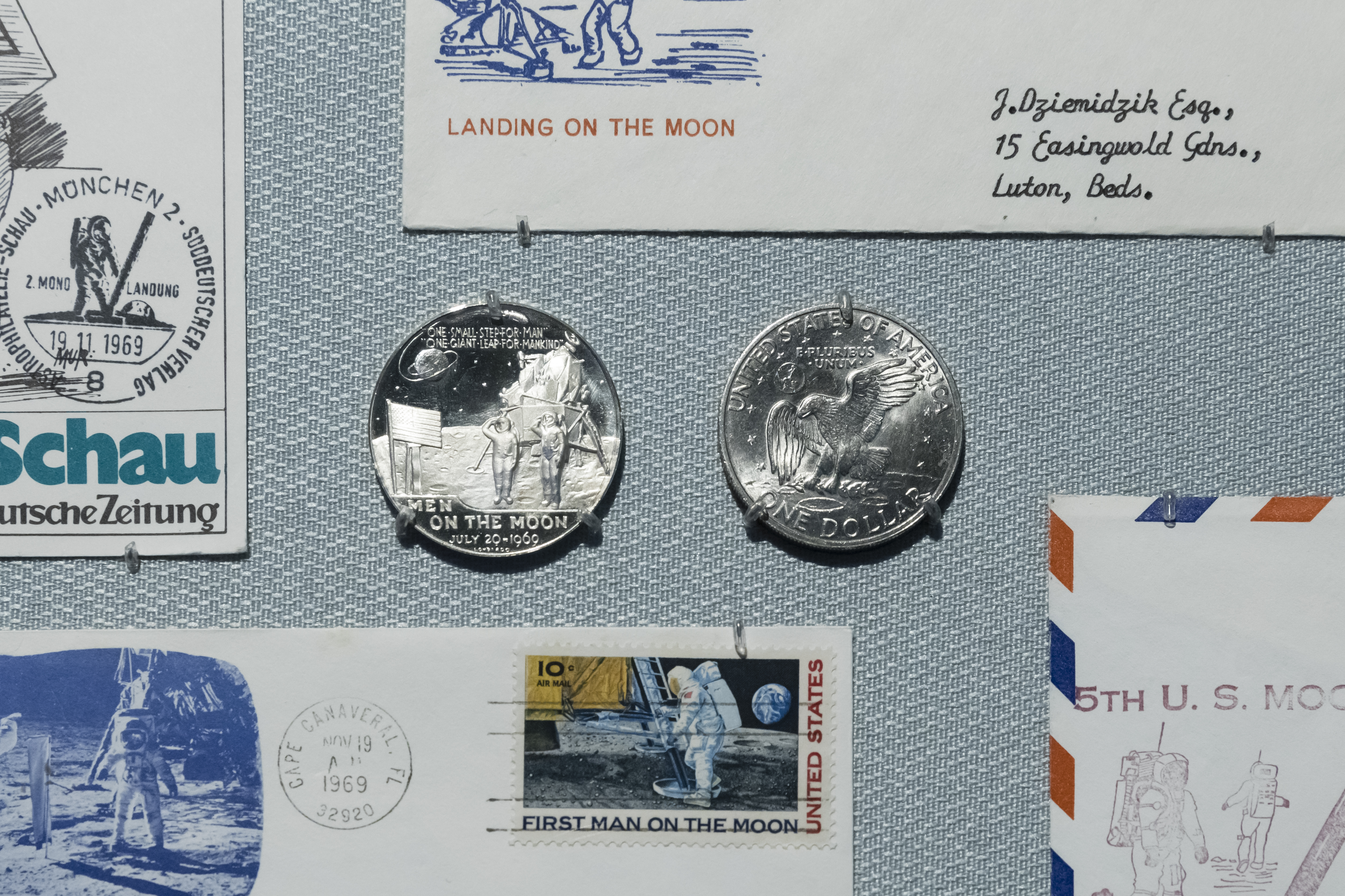 Two small silver medallions, surrounded by commemorative envelopes, all bearing imagery from the Apollo 11 mission.