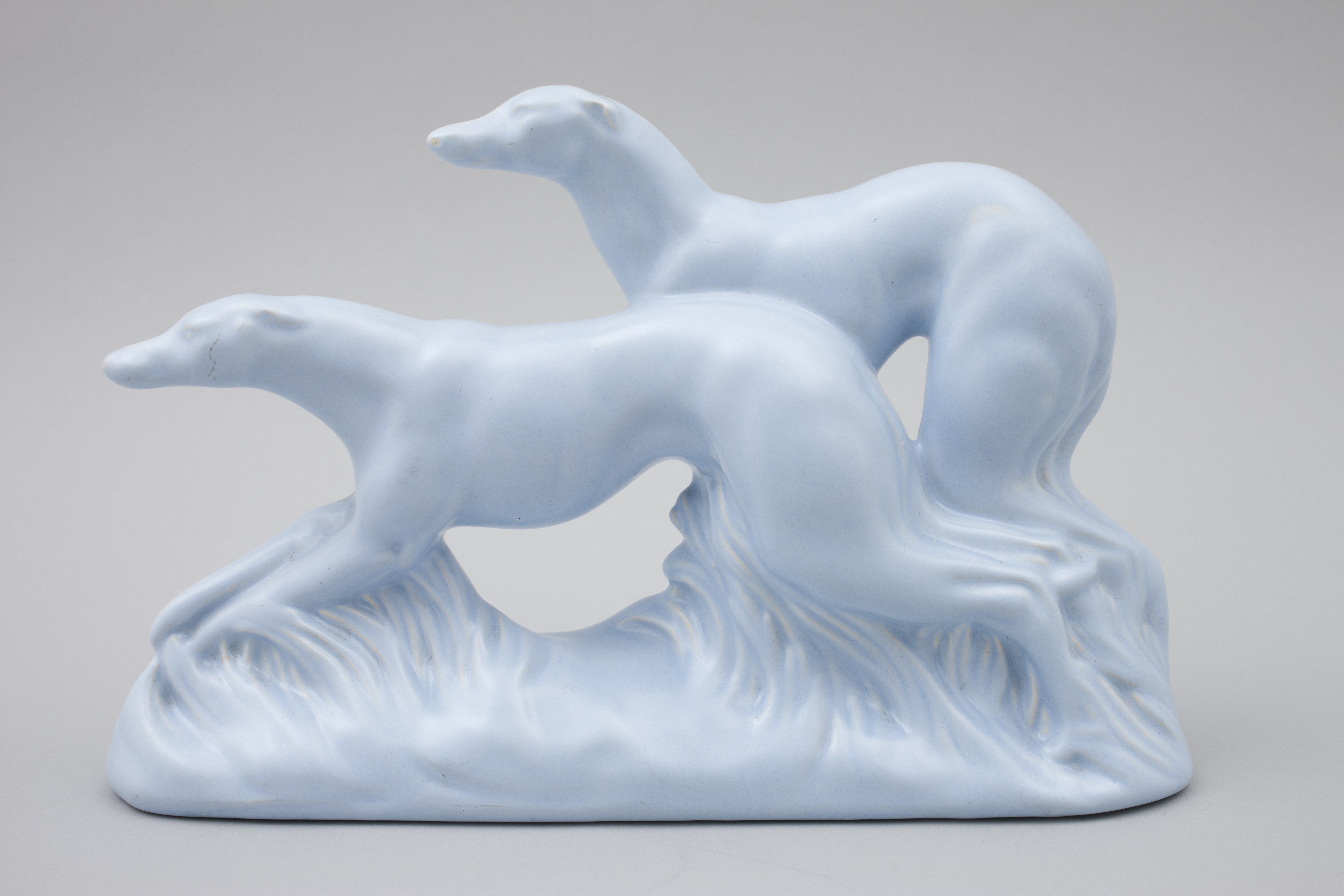 An earthenware figure of two greyhound. The entire figurine is blue glazed and the greyhounds are in a running pose.