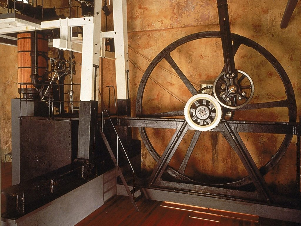 A museum display of an open steam engine made up of a large fly wheel attached by gears to a piston and steam cylinder.