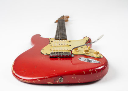 The guitar is a slab-board electric guitar, with a bolt-on neck. The headstock and neck is maple, and the fret-board is rosewood. The Fender decal is original 'spaghetti' style. It is a 22 fret neck with original clay dot inlays. The tremolo is synchronised and the machine heads are nickel Kluson. Three single-coil pickups with a three-way switch, two tone and one volume control. The pick-guard is triple layered mint. The colour of the body is Dakota Red. It has severe road-wear.
