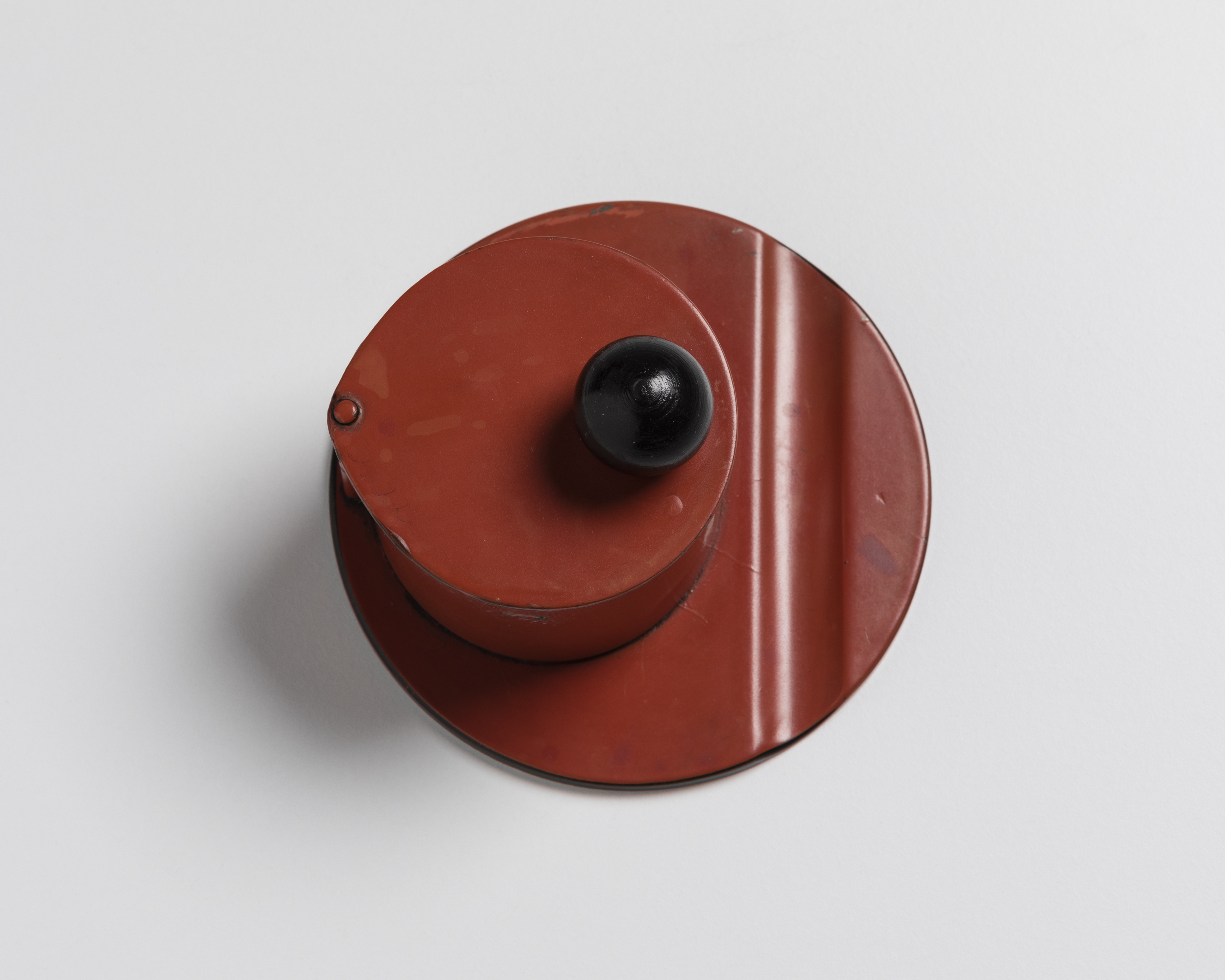 Red circular inkstand with a black ball finial on hinged cover, photographed from above.