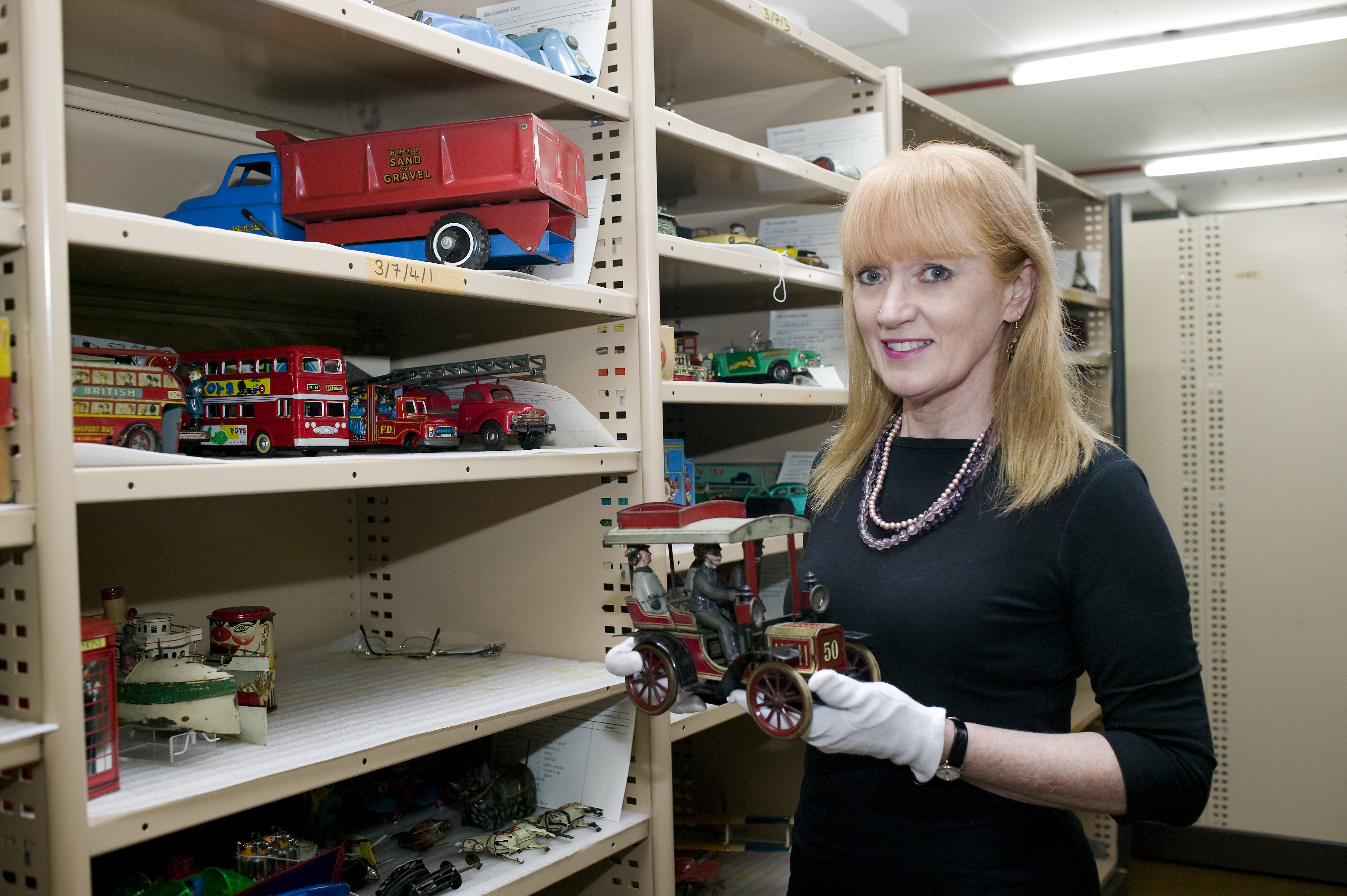A woman holds a 1920s-style model car toy. She is standing in front of industrial shelving, which holds a variety of toy cars, buses and trucks.