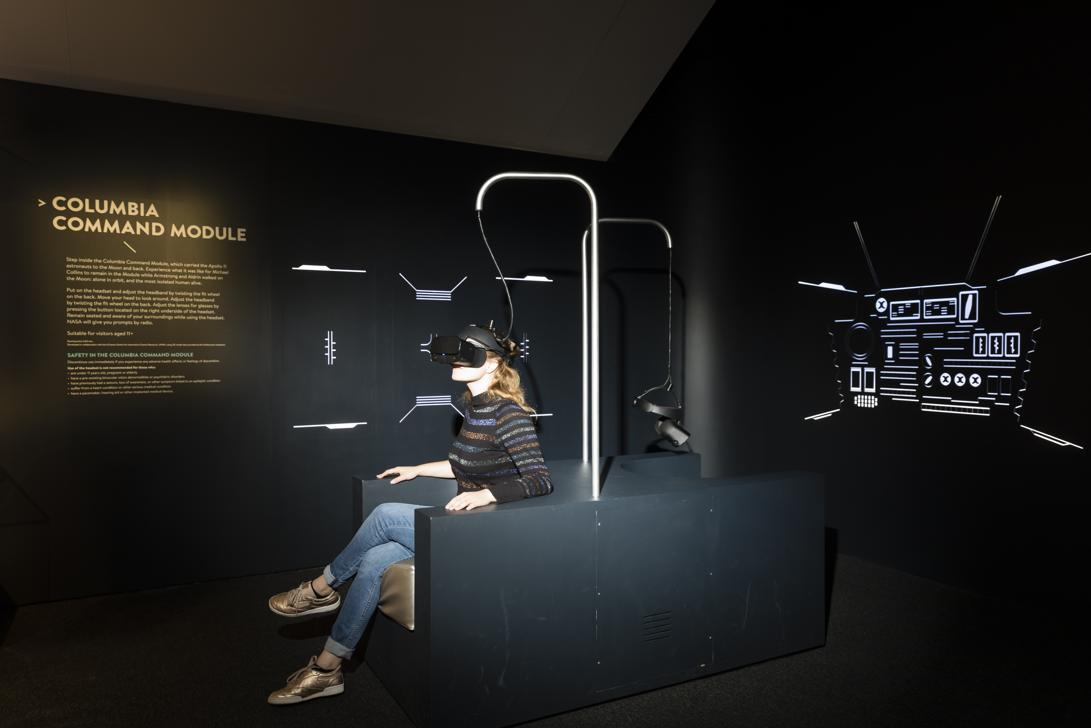 Dark nook with two seats built back-to-back. Above each seat dangles a VR headset attached to a metal pole. A woman sits in one seat wearing the headset. On the walls is an instructional text panel and backlit schematics of the Columbia control panels.