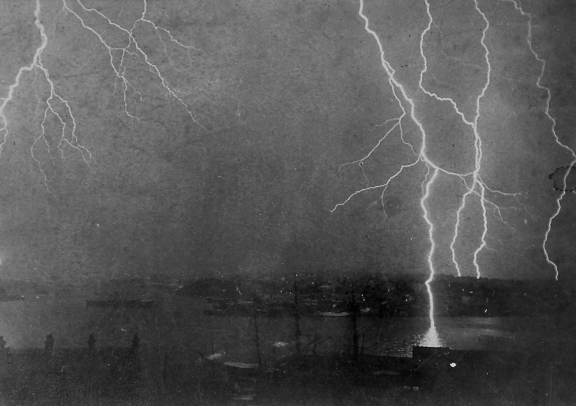 Black and white photograph depicting a lightning strike at night. The top two-thirds of the image is filled by sky with multiple, branching bolts of lightning. In the foreground can faintly be seen various buildings and a body of water beyond.