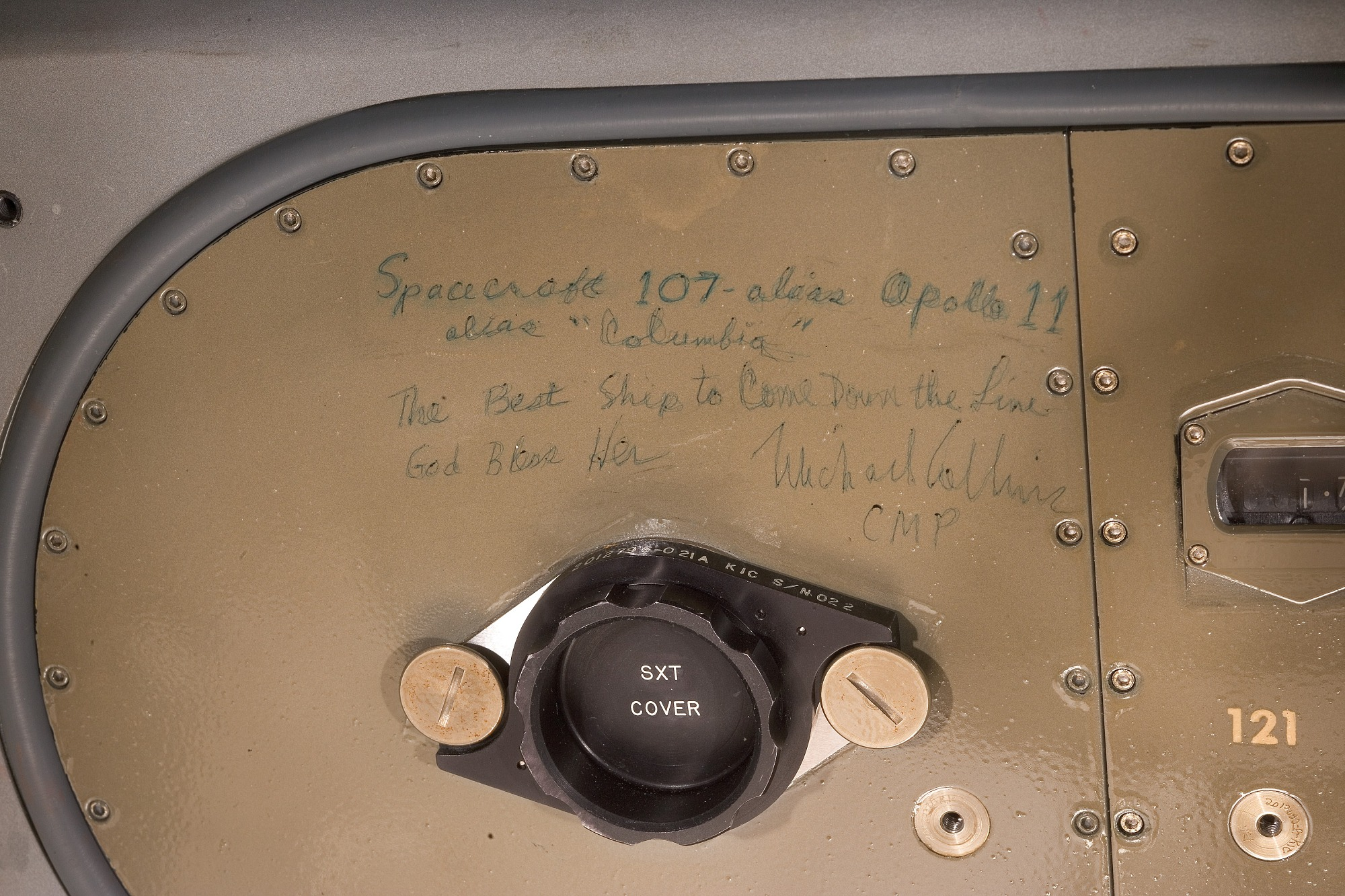 "Metal panel with rivets around the edge. Handwritten text in green ink reads: 'Spacecraft 107 – alias Apollo 11 / alias ""Columbia"" / The Best Ship to Come Down the Line / God Bless Her / Michael Collins / CMP'."