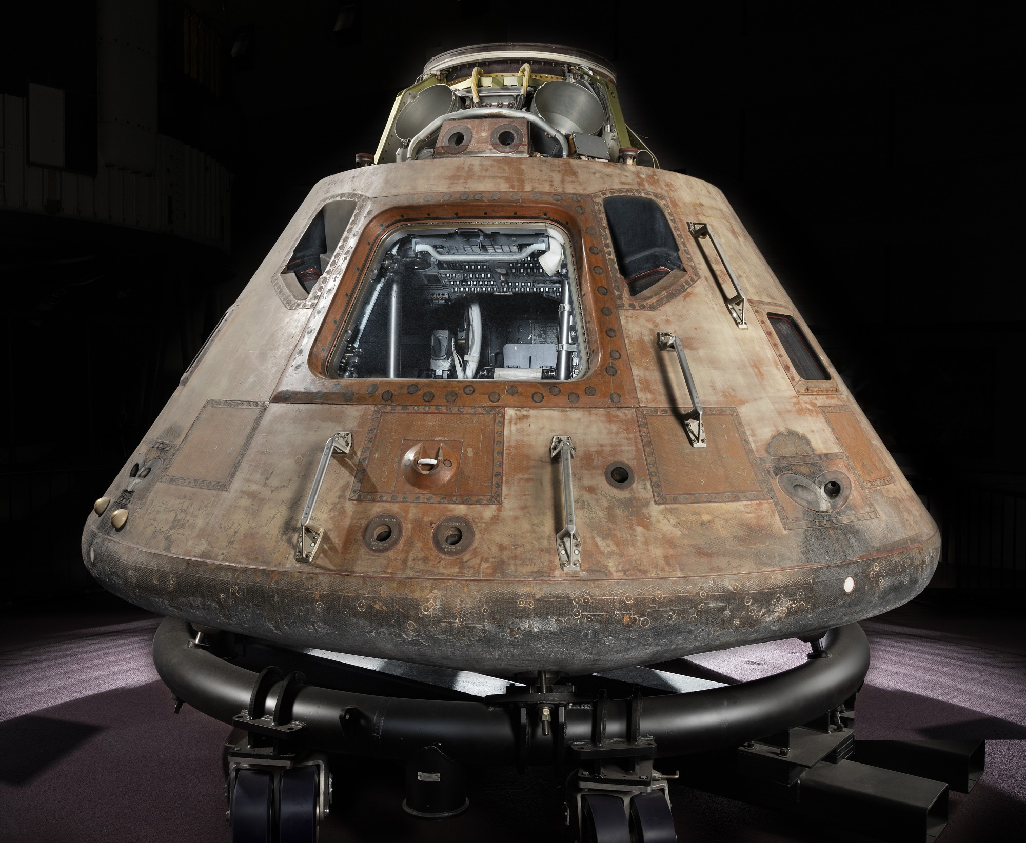 Conical-shaped spacecraft, photographed in a studio, constructed from numerous metal panels riveted together, now a rusted brown colour. Closest to the viewer is a rectangular hatch, with several small 'side' windows.