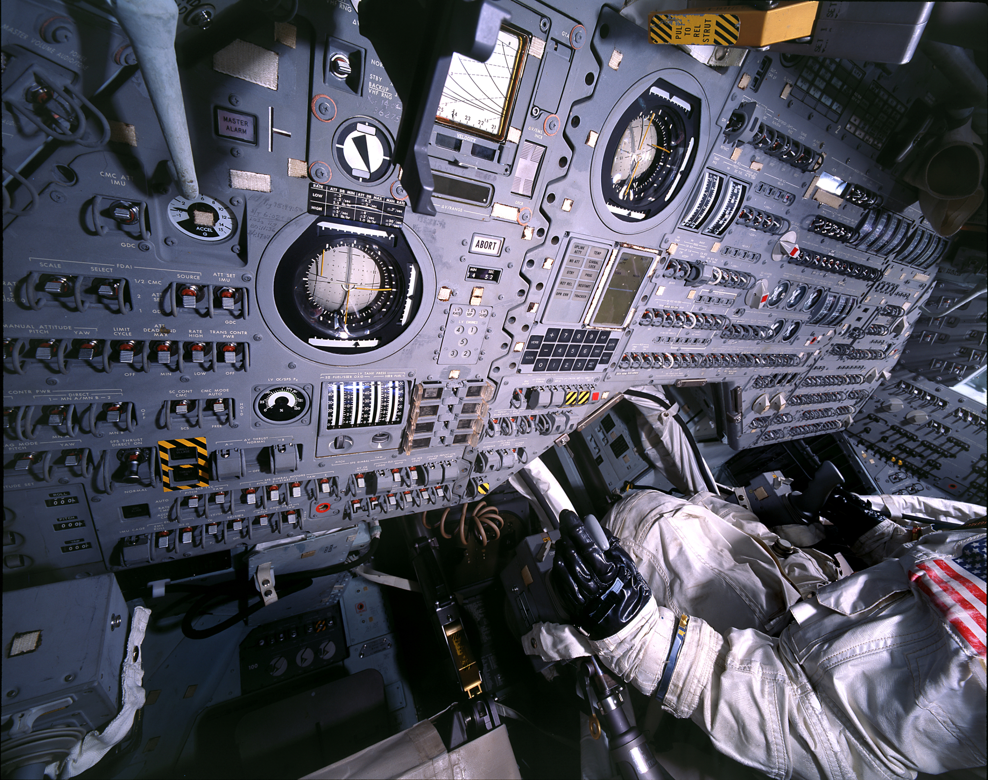 Close up of a control panel with innumerable buttons and switches. On the right mannequin of an astronaut sits, demonstrating the cramped conditions on board and the complexity of the spacecraft.