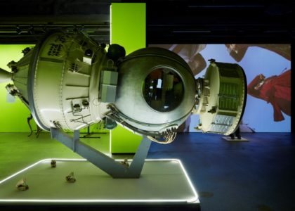 Exhibition view showing the Soviet era Cosmos‑782 Bion satellite in the foreground with selection of models from casts of horse jaws made, in the background is a detail of the Porkhani video by Javad Azimi and Hamid Hosseini. The walls in the space are painted a fluoro, hi-vis yellow and have led strip lighting.