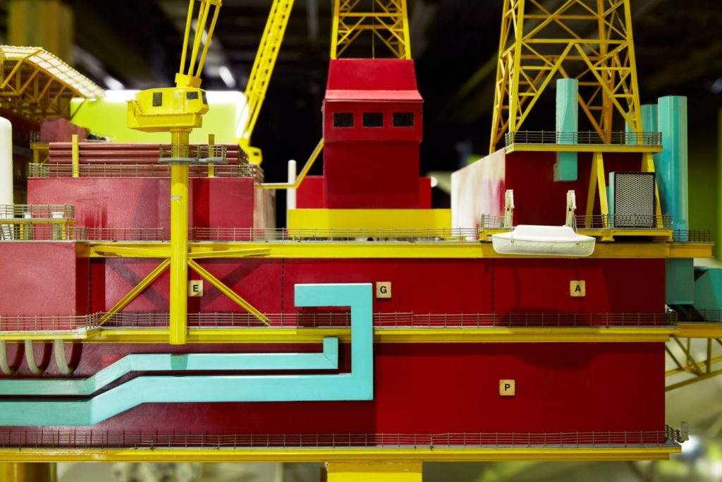 Detail of the Brent C model offshore oil rig, show lifeboat, details of cranes and other machinery on the platform in red, yellow and aqua colours.