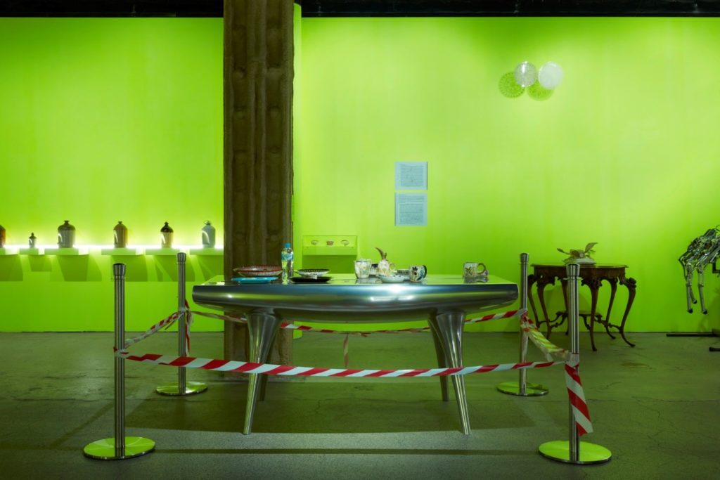 Exhibition view with an aluminium table in the foreground. Different ceramics are arranged on the table, which has hazard tape around its perimeter. In the background are ceramic bird feeders an antique wooden table and silk worm moth model.