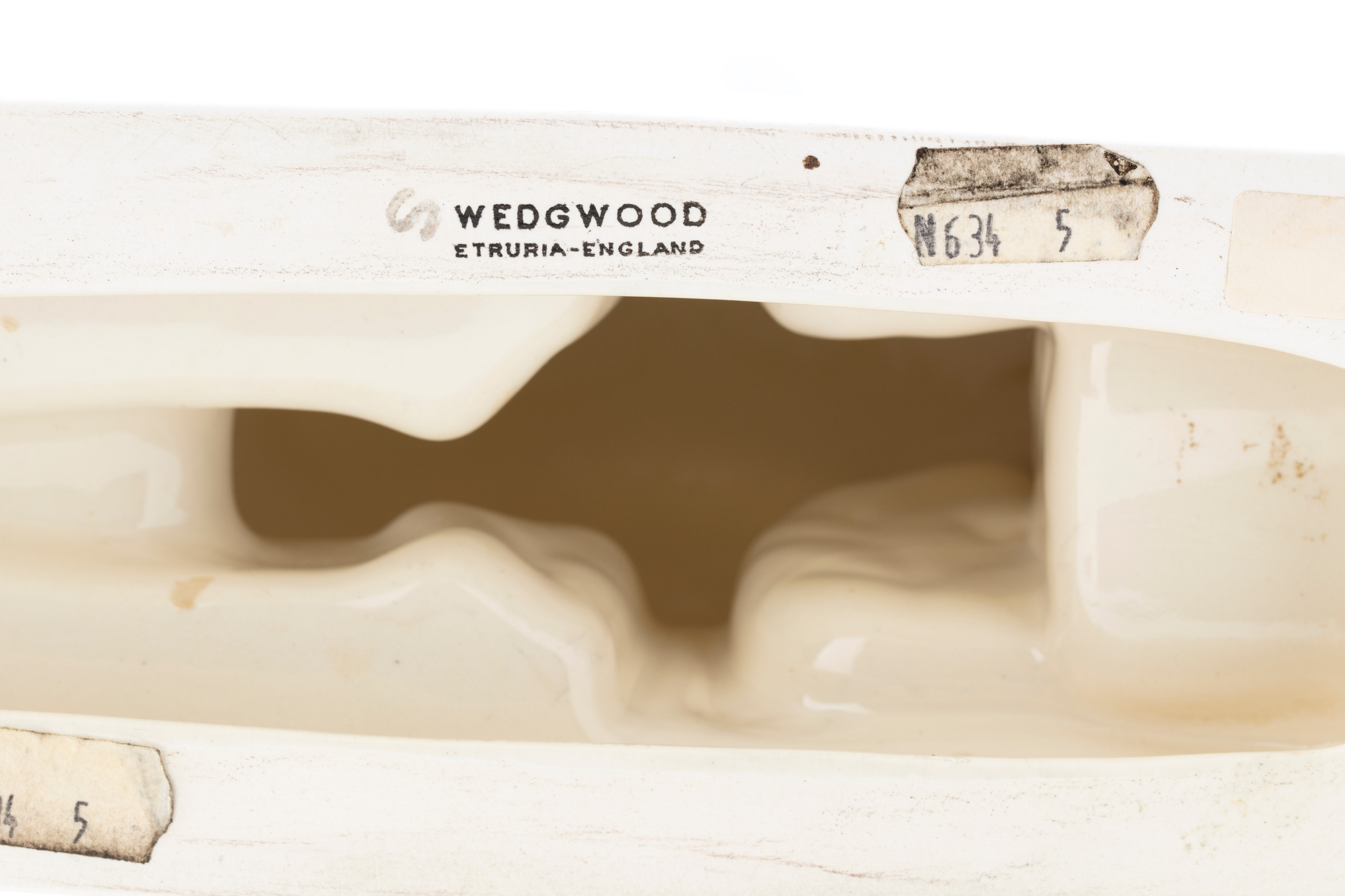 Underside of a white earthenware figure showing the printed black text 'WEDGWOOD / ETRURIA-ENGLAND'.