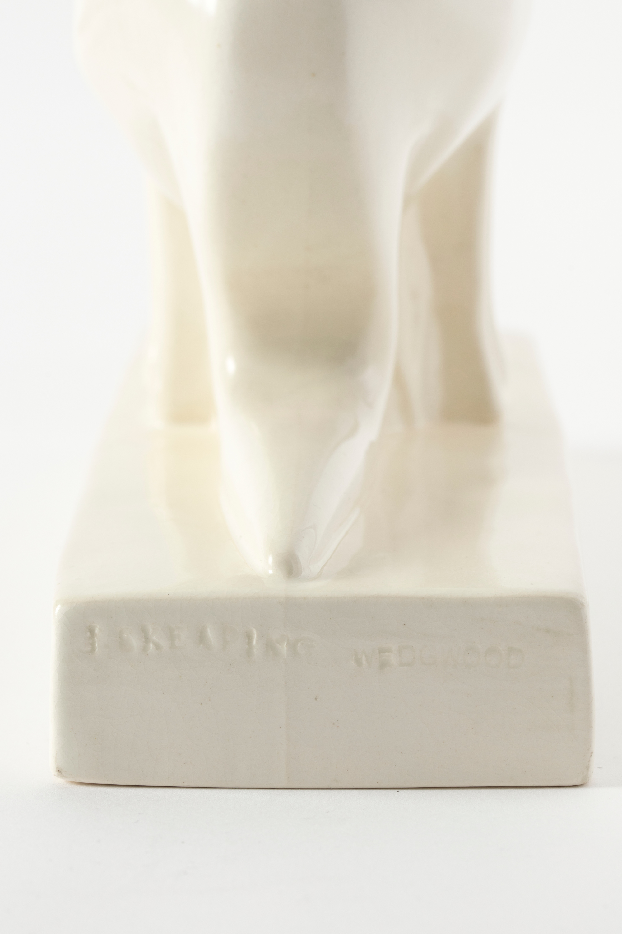 Rectangular base of a white earthenware figure showing the imprinted text 'J SKEAPING / WEDGWOOD'.