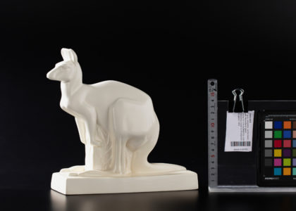White earthenware kangaroo on a black studio background. To the right of the kangaroo is a upright metal ruler (for scale), paper object tag, and colour reference chart. The kangaroo is about 20cm tall.