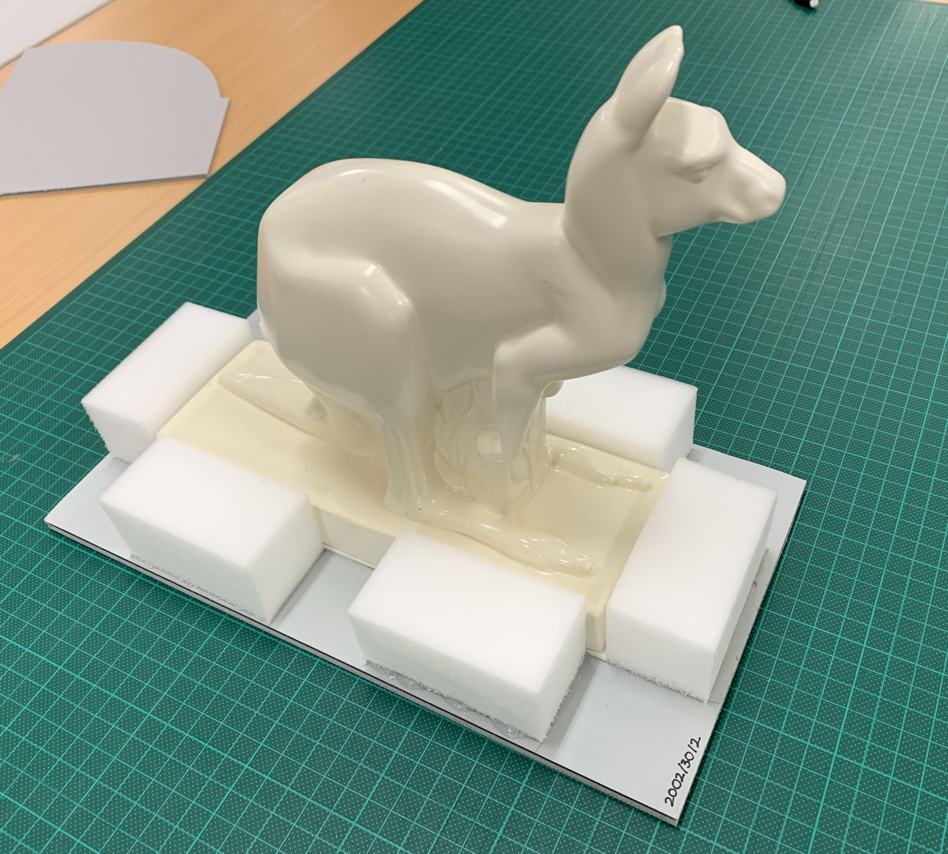 White earthenware kangaroo sitting on a stiff plastic base. The kangaroo figure itself has rectangular base around which have been glued six foam blocks – two each along the long sides of the base, and one each along the short sides.