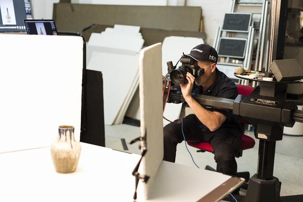 Digitisation Project photographer Marinco Kojdanovski at work in the studio photographing a ceramic object.