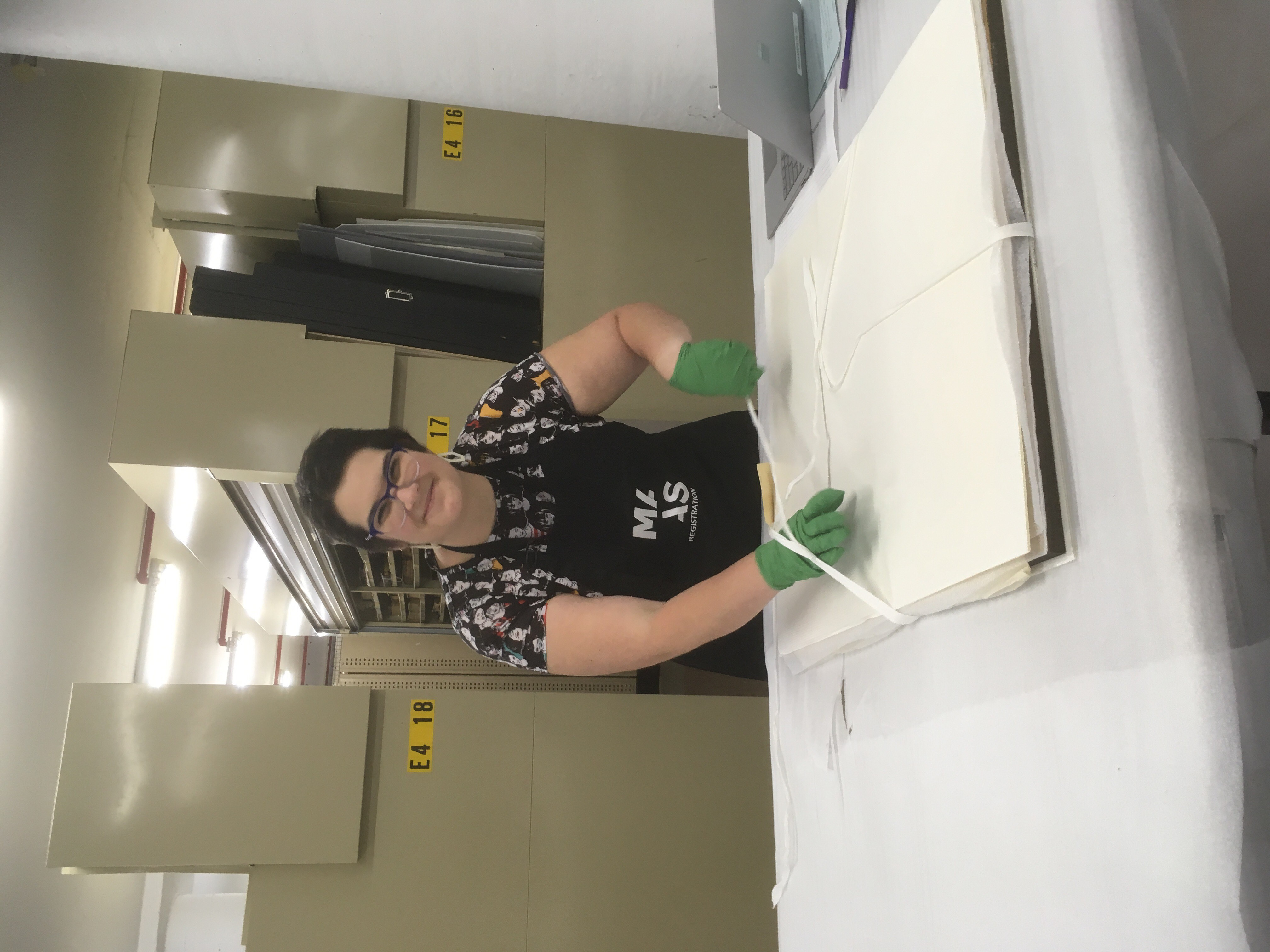 A woman in green latex gloves and a black apron with a 'MAAS' logo untying the fabric ribbon on a stack of paper works. A laptop is beside her and a row of compactus bays in the background.