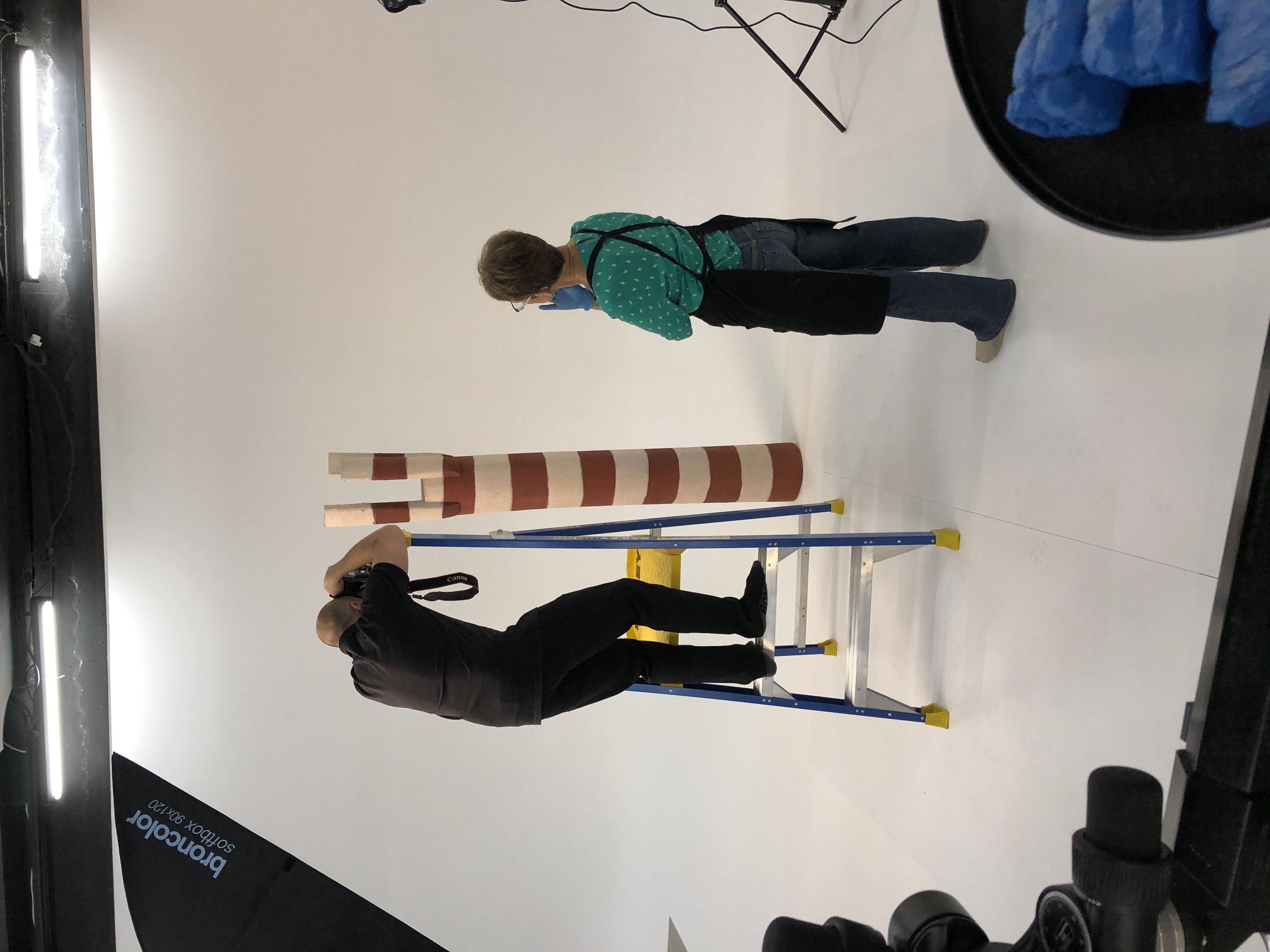 A man stands on a ladder photographing a hand-carved work in the shape of an upturned tree. A woman wearing latex gloves and an apron stands to the side. Various photographic equipment can be seen around the edges of the image. Both are wearing socks.