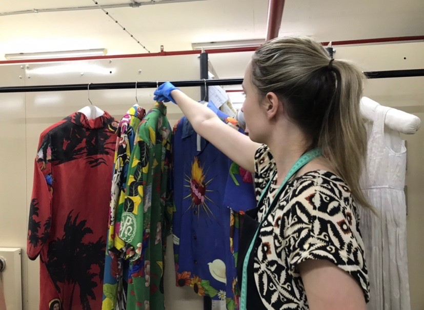 Photograph taken over the shoulder of a woman picking up a brightly coloured shirt from a clothes rack. The woman is wearing blue latex gloves and has a tape measure around her neck.