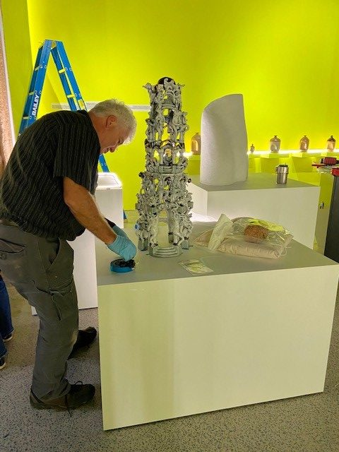 Conservator Tim Morris is finalising object supports for ceramics on open display plinths in gallery space. Ceramicist Brian Doar's 'Welcome to the Herb Alpert Pleasure Dome' artwork is in the foreground.